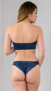 Closeup back view of model wearing reversible bikini bottom with ethereal dark blue water print on one side and textured watercolor print on the reverse side