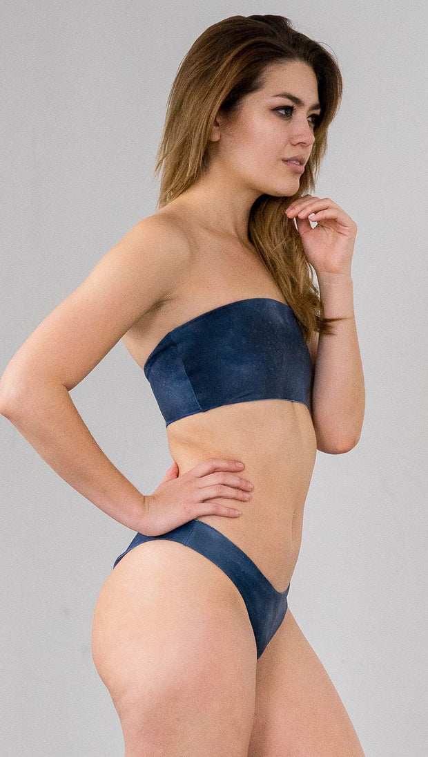 Closeup right side view of model wearing reversible bikini bottom with ethereal dark blue water print on one side and textured watercolor print on the reverse side