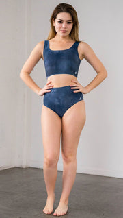 Front view of model wearing reversible high waist bikini bottom with ethereal dark blue water print on one side and textured watercolor print on the reverse side