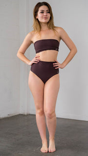 front view of model wearing reversible vintage inspired bikini bottom with woodgrain background and romantic rose clusters on one side and solid brown on the opposite side