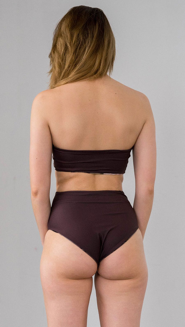 closeup back view of model wearing reversible vintage inspired bikini bottom with woodgrain background and romantic rose clusters on one side and solid brown on the opposite side
