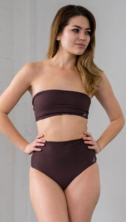 closeup front view of model wearing reversible vintage inspired bikini bottom with woodgrain background and romantic rose clusters on one side and solid brown on the opposite side