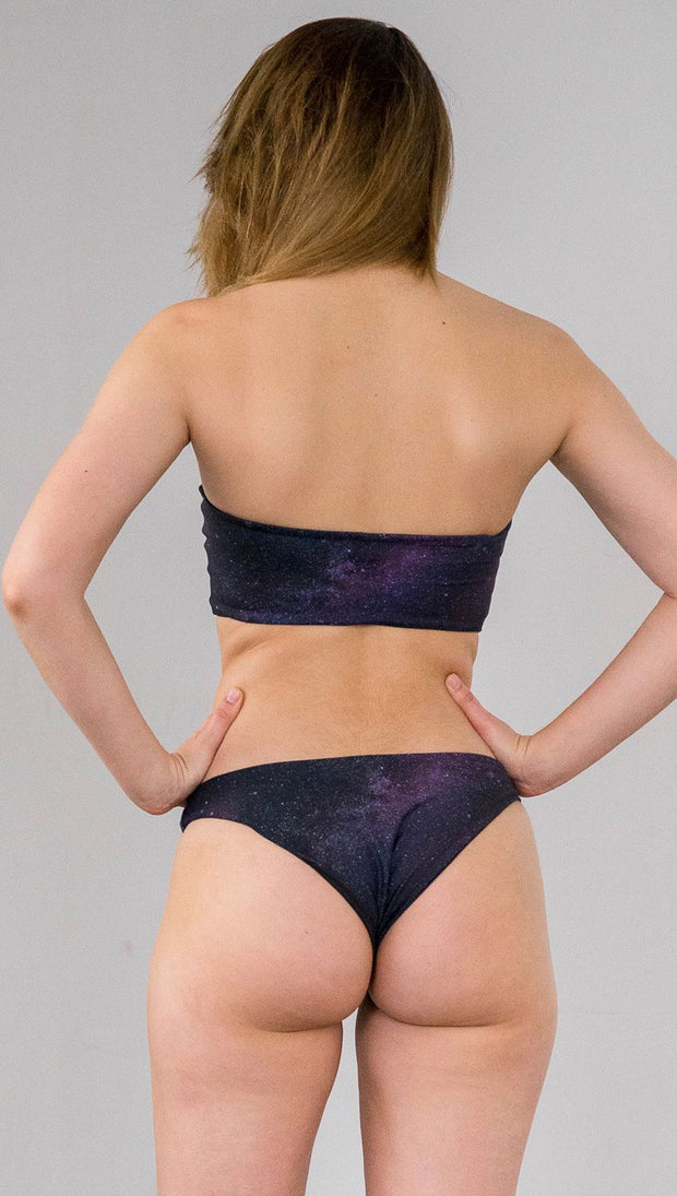 Closeup back view of model wearing reversible bikini bottom with celestial galaxy print on one side and black leather texture print on the opposite side