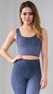 Three quarter length front view of a model wearing a blue mosaic tile print reversible crop top with dark gray mosaic tile print on the other side