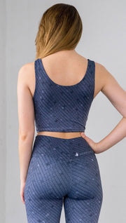 Three quarter length rear view of a model wearing a blue mosaic tile print reversible crop top with dark gray mosaic tile print on the other side