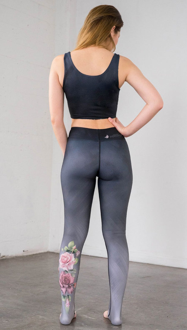 Full length rear view of model wearing full length black to gray ombre leggings with rose details and a matching crop top