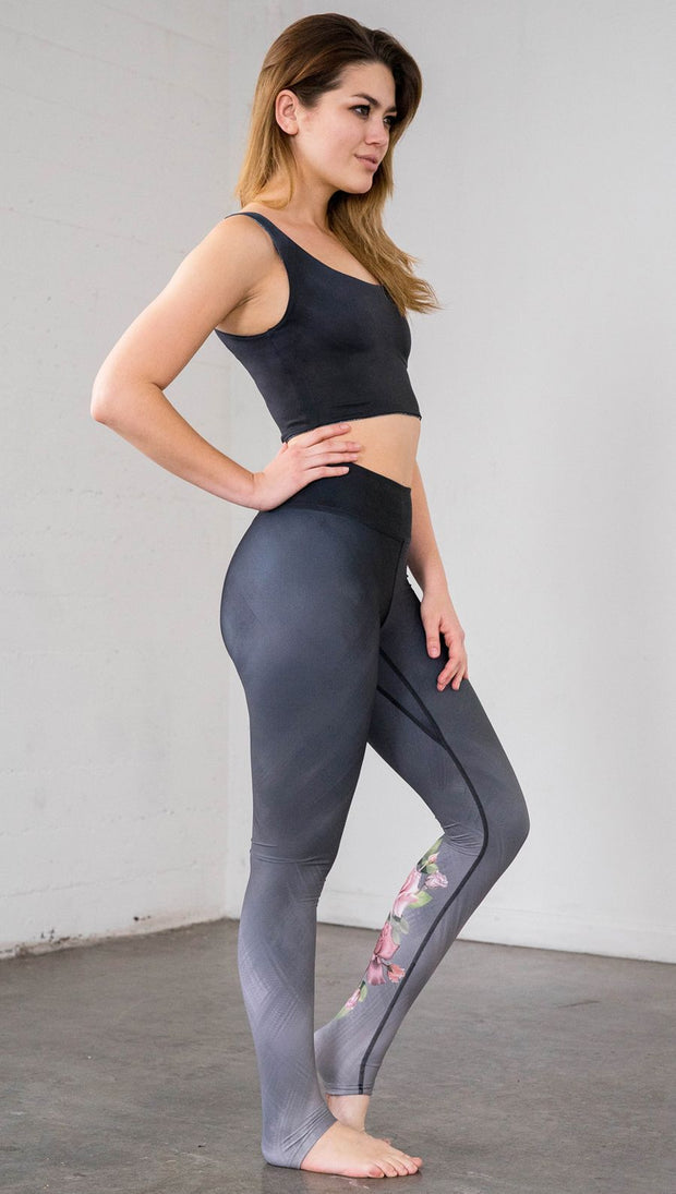 Full length right side view of model wearing full length black to gray ombre leggings with rose details and a matching crop top