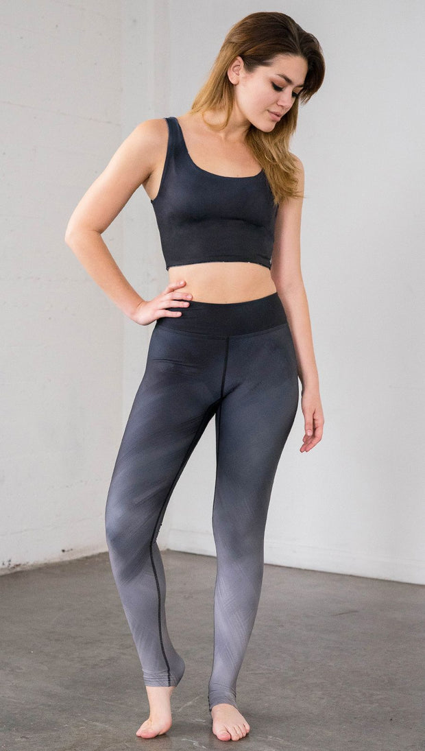 Full length front view of model wearing full length black to gray ombre leggings with rose details and a matching crop top