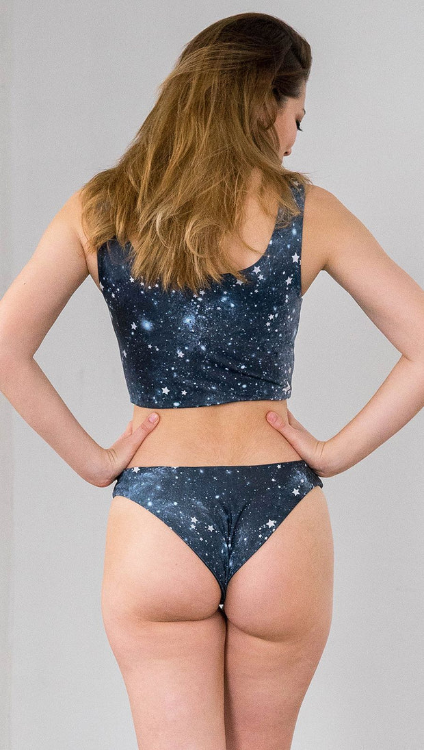closeup back view of model wearing reversible bikini bottom with starry night galaxy celestial print on one side and black brushstrokes on the opposite side.
