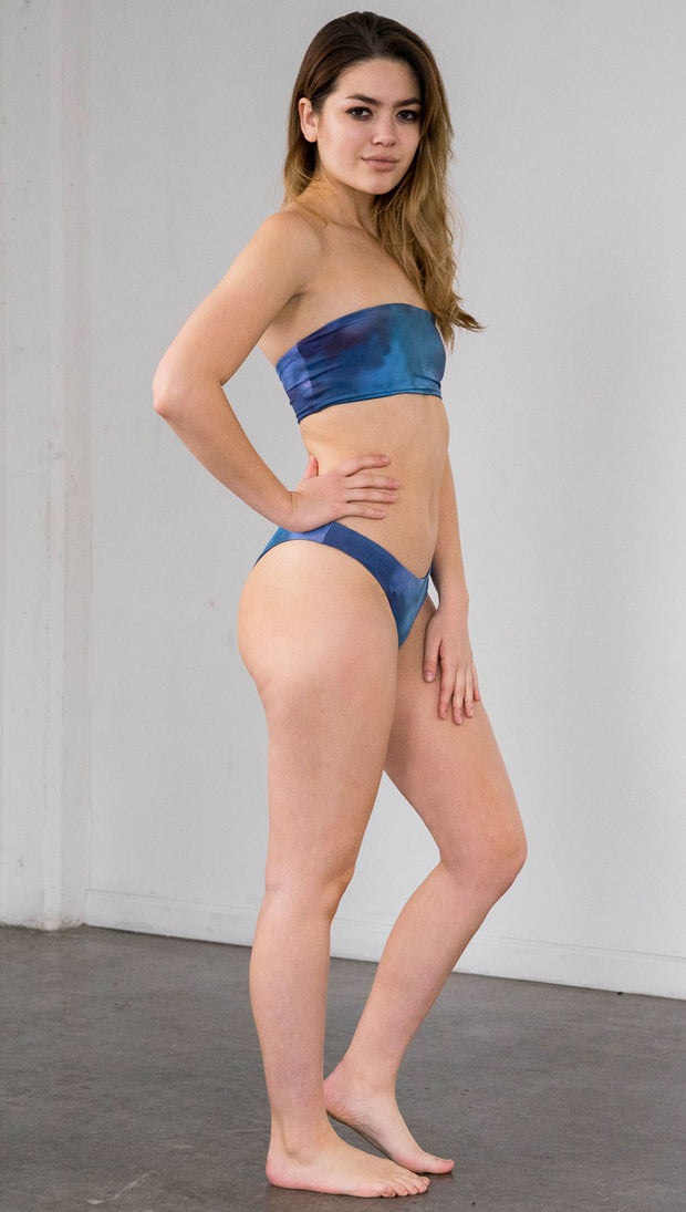 Right side view of model wearing reversible bikini bottom with ethereal dark blue water print on one side and textured watercolor print on the reverse side