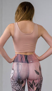 Three quarter length rear view of model wearing a reversible beige/light skin tone crop top with a light brown/medium skin top on the inside