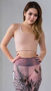 Three quarter length front view of model wearing a reversible beige/light skin tone crop top with a light brown/medium skin on the inside