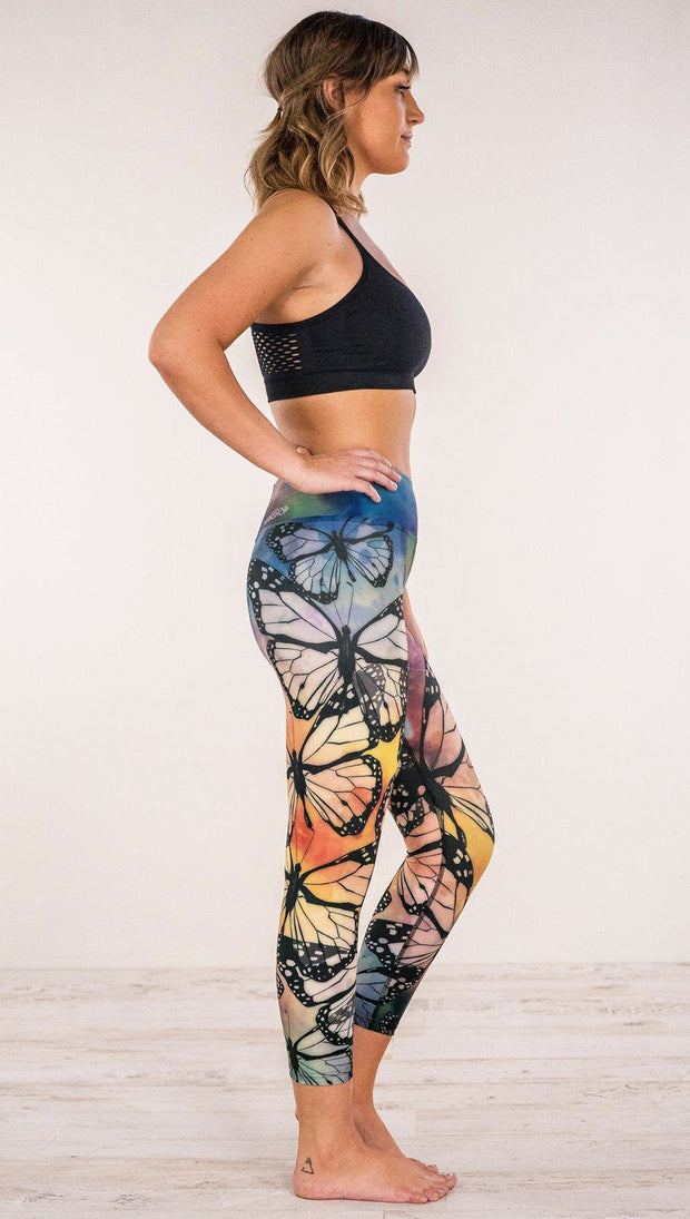 Right side view of model wearing rainbow butterfly themed printed capri leggings