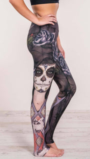 Close up right side view of model wearing sugar skull themed printed full length leggings