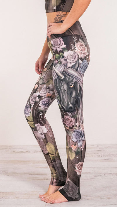 Close up side view of model wearing unicorn and rose printed full length leggings