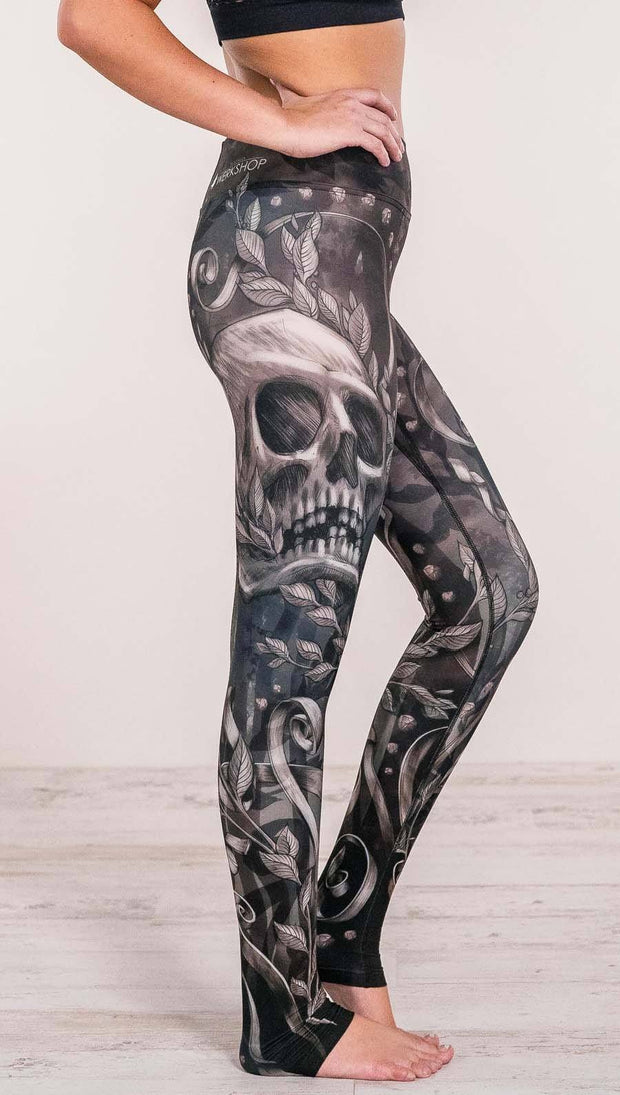Close up right side view of model wearing gothic themed printed full length leggings