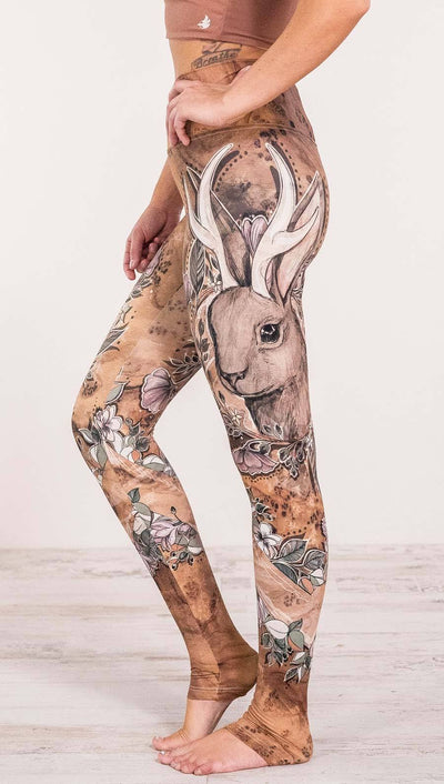 Close up left side view of model wearing full length leggings with printed jackalope design