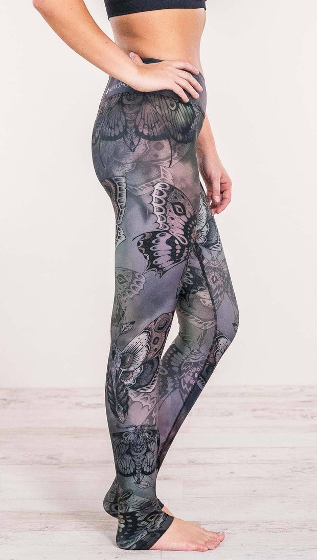 Close up right side view of model wearing full length printed leggings with gothic moths, gargoyles, skulls, ravens design