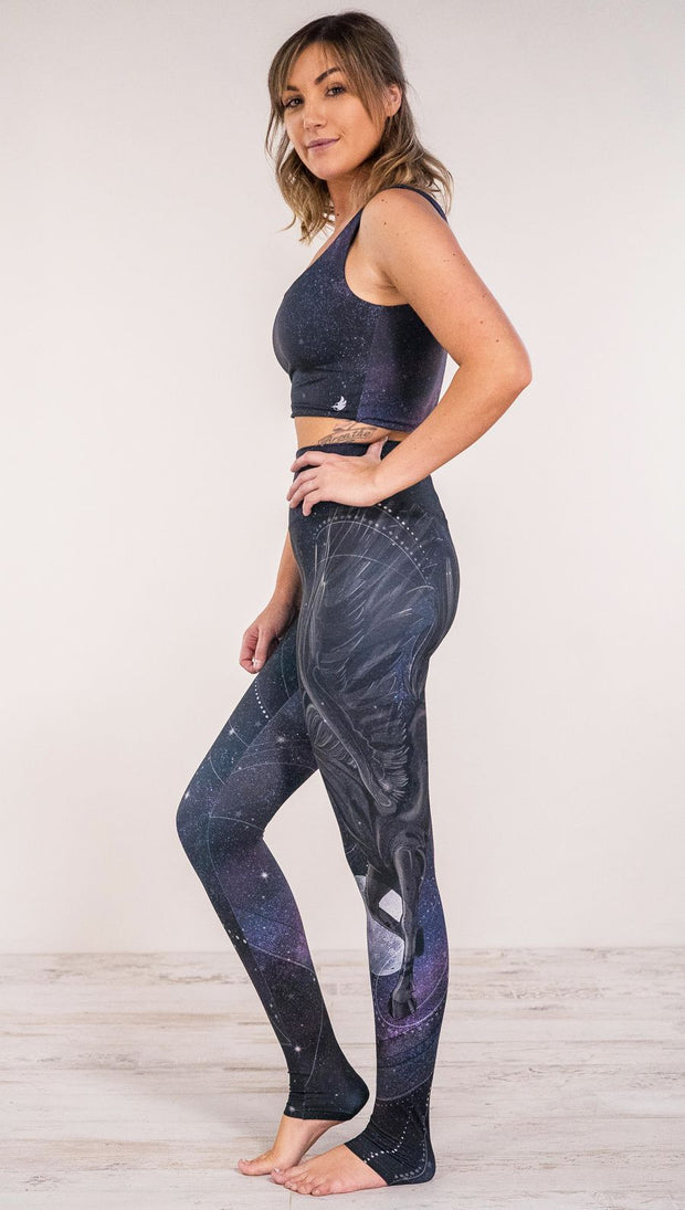 Side view of model wearing fantasy flying pegasus themed printed full length leggings