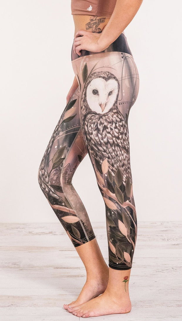 Close up side view of model wearing owl themed leggings