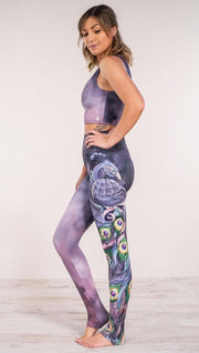 Side view of model wearing peacock themed full length leggings