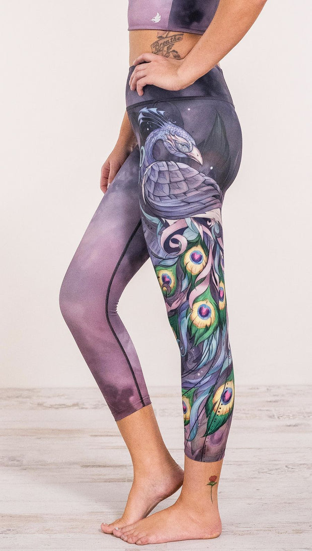 Close up side view of model wearing peacock themed leggings