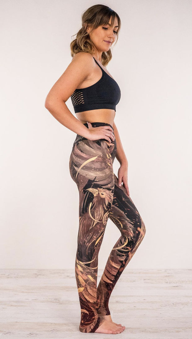 Side view of model wearing phoenix themed full length leggings