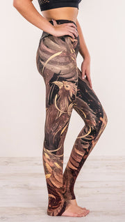 Close up side view of model wearing phoenix themed full length leggings