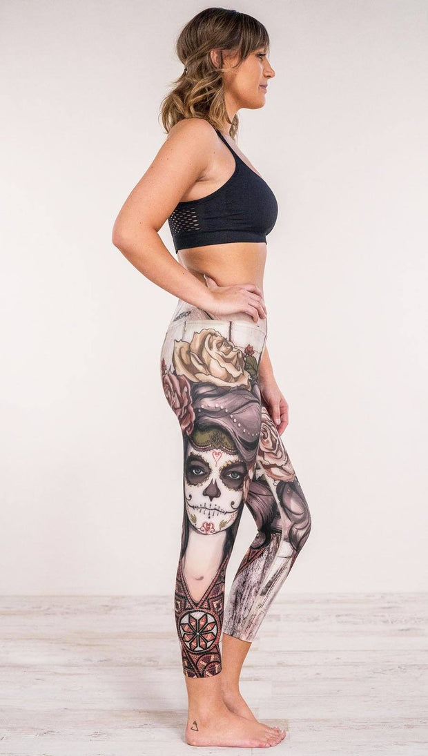 Right side view of model wearing sugar skull themed printed capri leggings