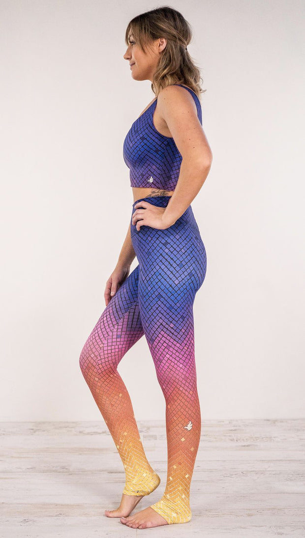 Side view of model wearing purple/pink/yellow ombre mosaic tile print full length leggings