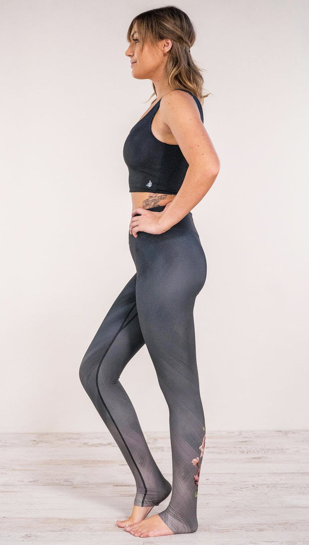 Left side view of model wearing rose themed full length leggings