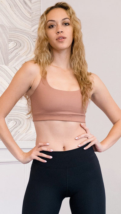 front view of model wearing brown cinnamon colored sports bra