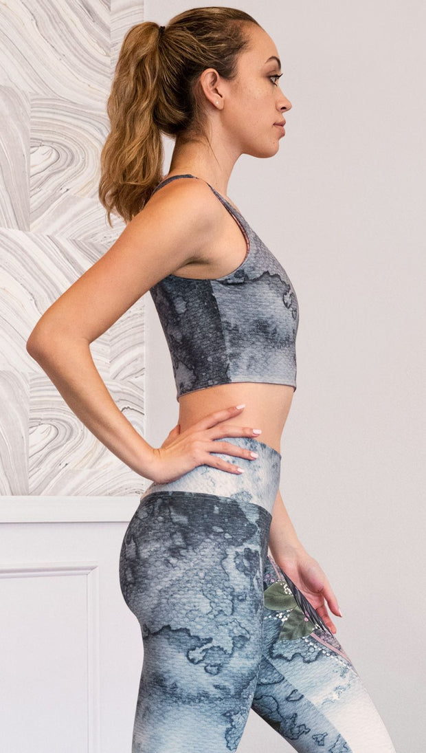 right side view of model wearing watercolor artwork themed reversible sports top