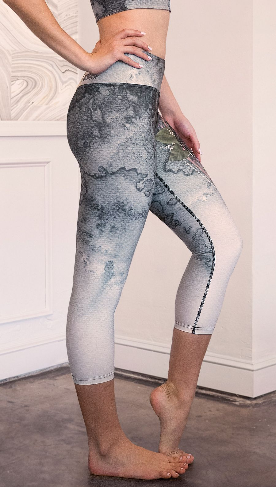 closeup left side view of model wearing capri Finnish Lapphund artwork themed leggings