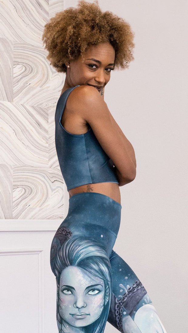 Right side view of model wearing reversible tank top with ethereal dark blue water print on one side and textured watercolor print on the reverse side