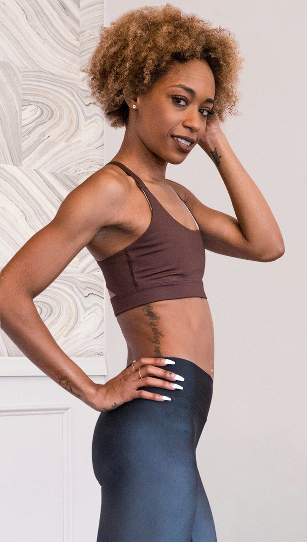 right side view of model wearing nude / mocha tone sports bra