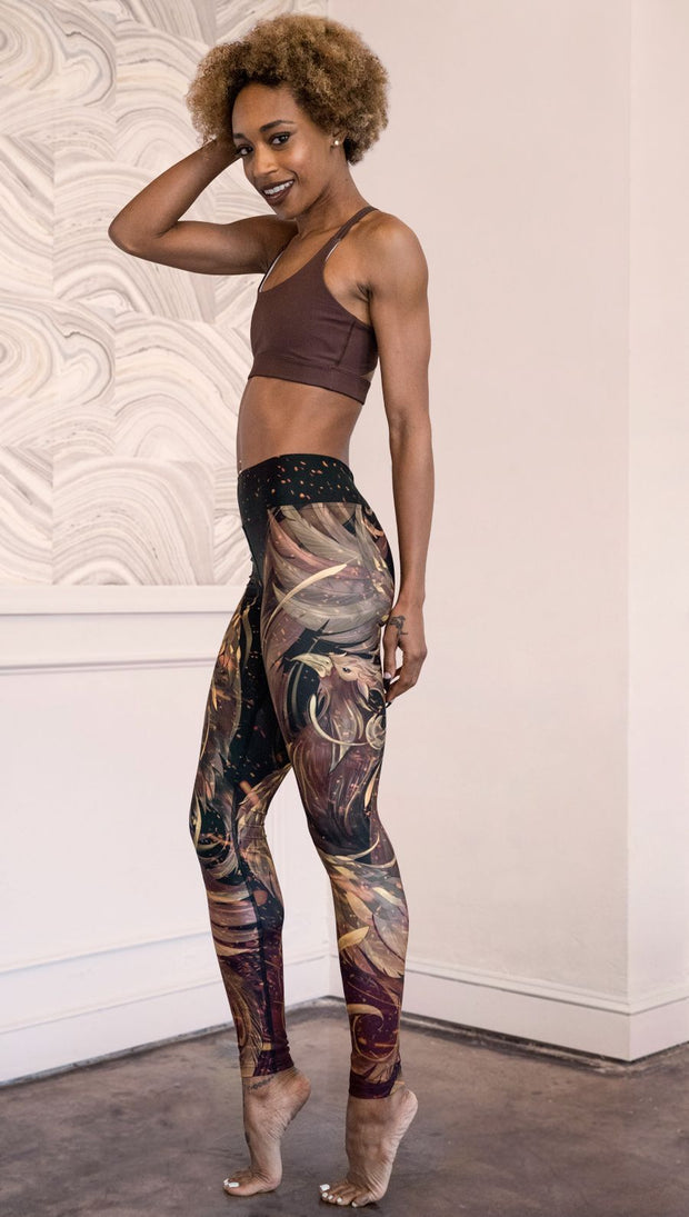 left side view of model wearing phoenix themed full length leggings