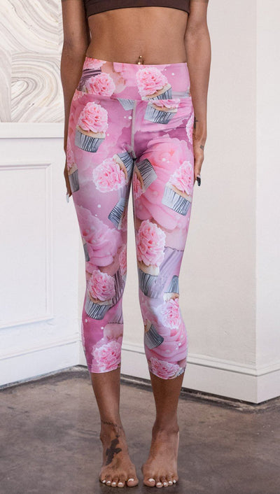 closeup front view of model wearing pink cupcake design printed capri leggings