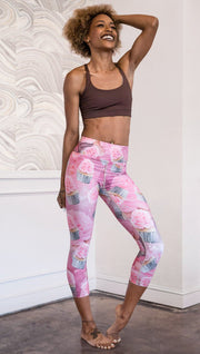 front view of model wearing pink cupcake design printed capri leggings