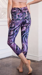 closeup backup view of model wearing cupcake themed capri leggings with purple and royal blue frosting and rainbow colored sprinkle design