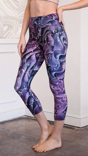closeup left side view of model wearing cupcake themed capri leggings with purple and royal blue frosting and rainbow colored sprinkle design