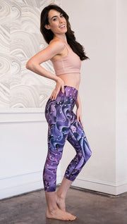 right side view of model wearing cupcake themed capri leggings with purple and royal blue frosting and rainbow colored sprinkle design