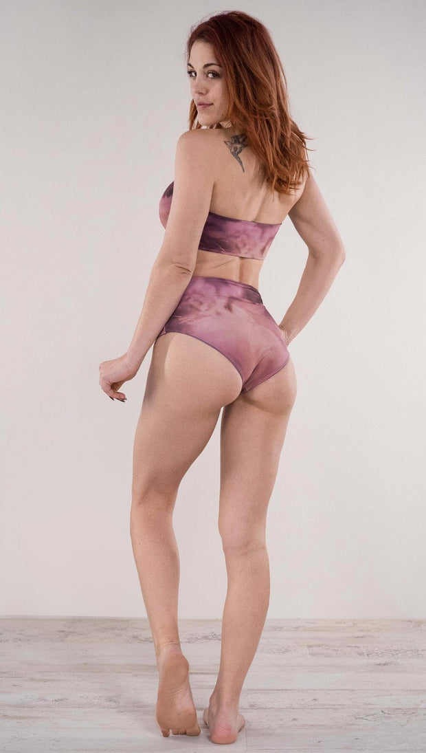 Back side view of model wearing the reversible Peacock high waist bikini bottom in the Rose Quartz side in the colors pink and purple