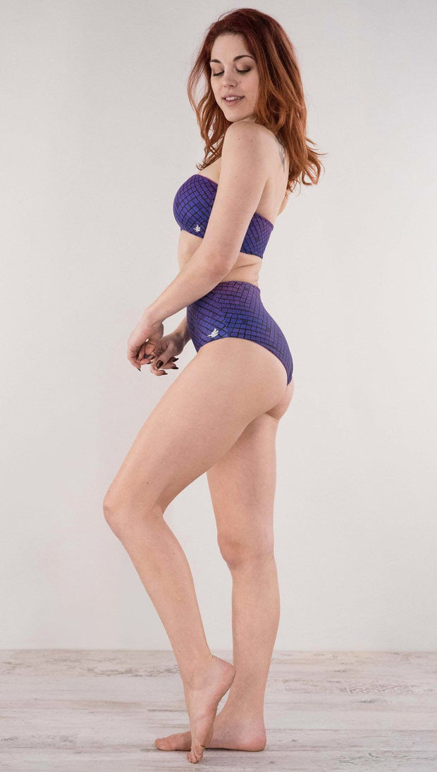 Left side view of model wearing the reversible Rainbow Mosaic high waist bikini bottom in the mosaic tile side in the color purple