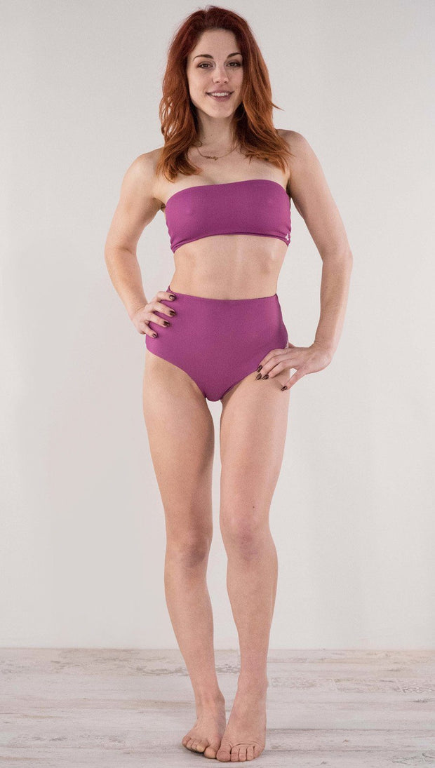 Front view of model wearing the reversible Rainbow Mosaic high waist bikini bottom in the reversed fuchsia side