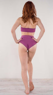 Back view of model wearing the reversible Rainbow Mosaic high waist bikini bottom in the reversed fuchsia color