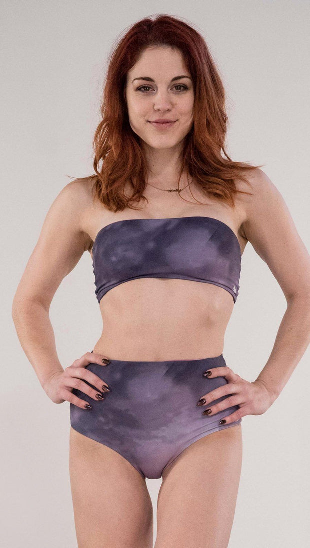 Front view of model wearing the reversible Peacock high waist bikini bottom in the Peacock side in the colors purple and dark purple