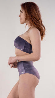 Left side view of model wearing the reversible Peacock high waist bikini bottom in the Peacock side in the colors purple and dark purple