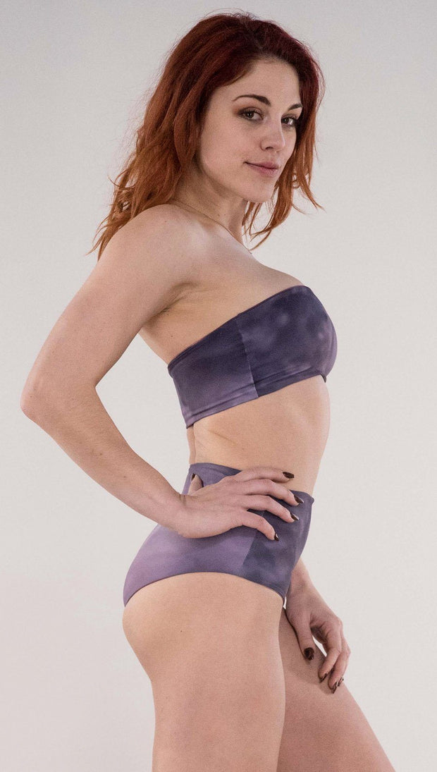 Right side view of model wearing the reversible Peacock bandeau in the Peacock side in the colors purple and dark purple