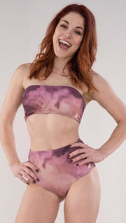 Front view of model wearing the reversible Peacock high waist bikini bottom in the Rose Quartz side in the colors pink and purple